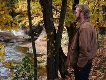 Man looking at ravine. Man observing autumn scene - creek with cataract stock photo