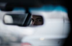 Man looking in the rear view mirror while driving Royalty Free Stock Photography