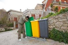 Man looking into recycle bin. Man looking into coleroed recycle bin Stock Photo