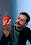 Man looking on a red apple. Picure of a Man looking on a red apple Stock Image