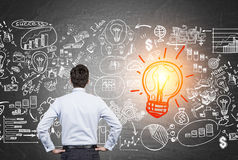 Man looking at red light bulb with business icons Royalty Free Stock Image