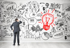 Man looking at red light bulb sketch Royalty Free Stock Photos