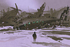 Man looking at remains of destroyed planes in snow Stock Images