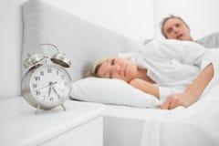 Man looking at ringing alarm clock. As his wife is still asleep Royalty Free Stock Image
