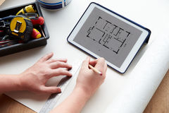 Man Looking At Room Plans On Digital Tablet Stock Photos