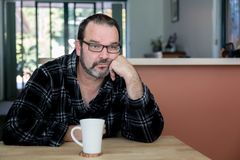 Man looking sad/depressed drinking his morning coffee royalty free stock photography