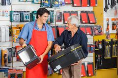 Man Looking At Salesman While Selecting Toolbox. Senior men looking at young salesman while selecting toolbox in hardware store Royalty Free Stock Photography