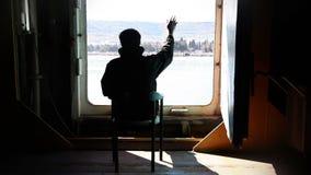 Man looking at sea and waving stock video footage