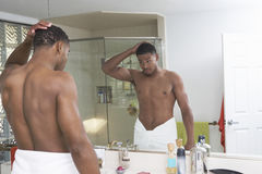 Man Looking At Self In Bathroom Mirror. Young African American man looking at self in bathroom mirror Royalty Free Stock Photos