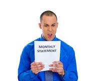 Man looking shocked and disgusted at his monthly statement Royalty Free Stock Photography