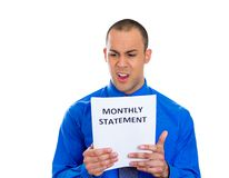 Man looking shocked and disgusted at his monthly statement Stock Photos