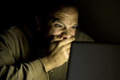 Man looking shocked on his laptop late at night Royalty Free Stock Image