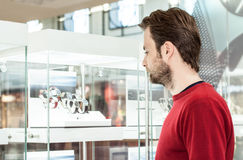 Man looking at shop window or display case in shopping center. Choosing a gift for woman Stock Photography