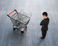 Man looking at shopping cart with light bulb top view. Standing man looking at shopping cart with large light bulb, on wooden floor background, high angle view Royalty Free Stock Photos