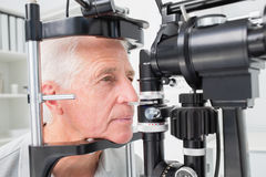Man looking into slit lamp Stock Photography