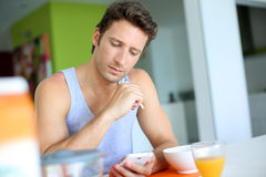 Man looking at smartphone during breakfast Stock Photography