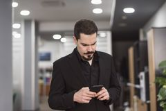 Man looking smartphone in office with suit clothing royalty free stock photography