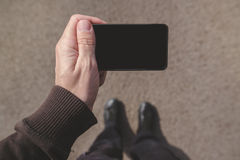 Man looking at smartphone screen while walking on street Stock Photography