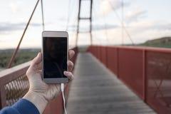 Man looking smartphone statistics pedestrian bridge over highway Stock Images