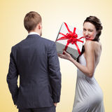 Man looking on smiling woman holding gift stock image