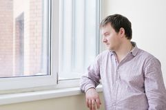 Man looking at snow into the window Royalty Free Stock Images