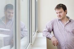 Man looking at snow into the window. Courageous middle age man looking at snow into the window Stock Photo