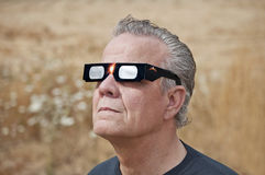 Man looking at the solar eclipse with eclipse glasses. Man viewing solar eclipse with solar glasses in country field Stock Photos