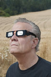 Man looking at the solar eclipse with eclipse glasses Stock Photos