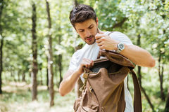 Man looking something in backpack at forest. Handsome young man looking something in backpack in forest Royalty Free Stock Photos