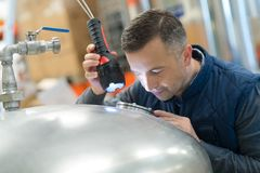 Man looking through stainless container Stock Photos