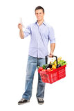 Man looking at store receipt and holding a basket Royalty Free Stock Images