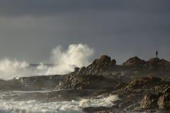 Man looking at stormy sea Stock Image