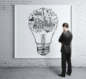 Man looking at success sketch. Thoughtful businessman looking at whiteboard with creative business sketch inside light bulb on whiteboard Success idea concept Royalty Free Stock Photography