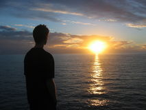 Man looking at sunset. Man looking into the sun going down into the sea Stock Photography