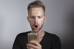 Man looking surprised at his phone. Man looking shocked to his mobile phone Royalty Free Stock Photo