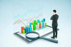 Man looking at tablet with chart. Thoughtful businessman looking at tablet with voluminous business chart and magnifying glass. Market analysis concept. 3D Stock Images