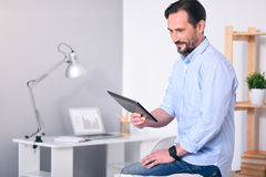Man looking at tablet in his hands. Nice day. Delighted bearded man looking with attention at the tablet in his hands while sitting on the back of a couch Stock Photography