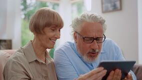 Man looking at tablet screen with woman.Grandparents using tablet for video call