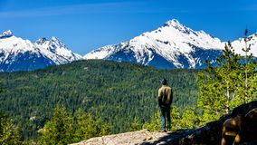 Man looking at the Tantalus Mountain Range. With snow covered peaks of Alpha Mountain, Serratus and Tantalus Mountain, seen from a viewpoint along the Sea to Royalty Free Stock Images