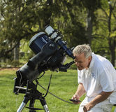 Senior man looking through telescope on Astronomy Day. An amateur astronomer looks through a telescope with a solar filter on Astronomy Day in Barrington, RI Stock Images