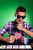 Man looking thoughtfully at his poker hand. Casual dressed young man looking thoughtfully at his poker hand, with full house on the poker table. Over green Stock Photos