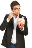 Man looking throught loupe to piggy bank Stock Photo