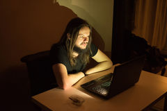 Man is looking to buy something through the internet. Handsome man in front of his computer in an obscure environment going through his computer, editing content Royalty Free Stock Photos