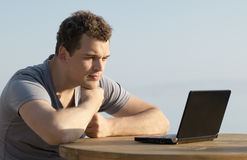 Man looking to the display of small laptop computer Royalty Free Stock Photos