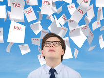 Man looking to falling tax papers Royalty Free Stock Image