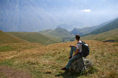 The man looking to the majestic mountais view. The man looking on the rock to the majestic mountais view stock images