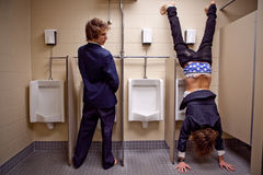 Man looking to an other man in a restroom doing werid things. Man looking to an other man upside down in a restroom stock photos
