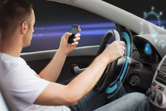 Man looking to smart phone while driving car Royalty Free Stock Photo