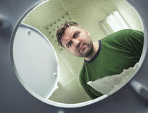 Man looking in the toilet bowl Royalty Free Stock Image