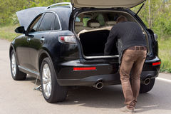 Man looking for tools in the boot of his car Royalty Free Stock Photos